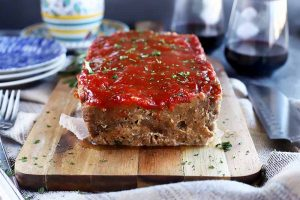 Horizontal image of meatloaf with ketchup glaze on a wooden cutting board, surrounded by colorful plates, a metal fork, a knife, and two glasses of wine.