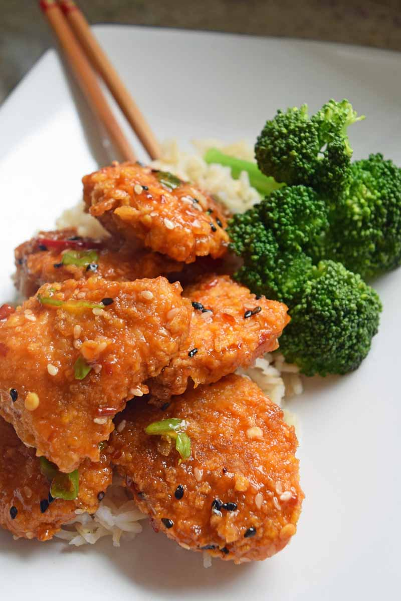 Oblique view of a white, square, porcelain platter full of a homemade baked General Tso's chicken and steamed broccoli.