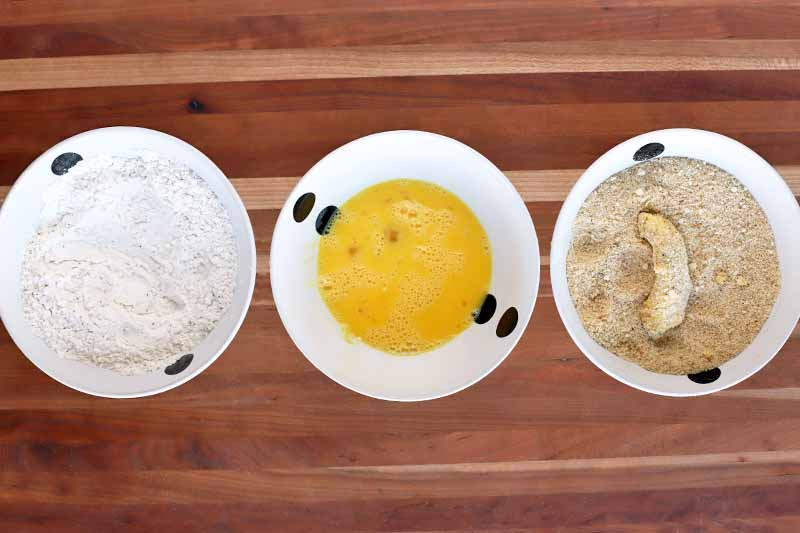 Overhead shot of three black and white bowls of flour, beaten egg, and breadcrumbs, with a wedge of avocado coated in the mixture in the third bowl, on a wood table.