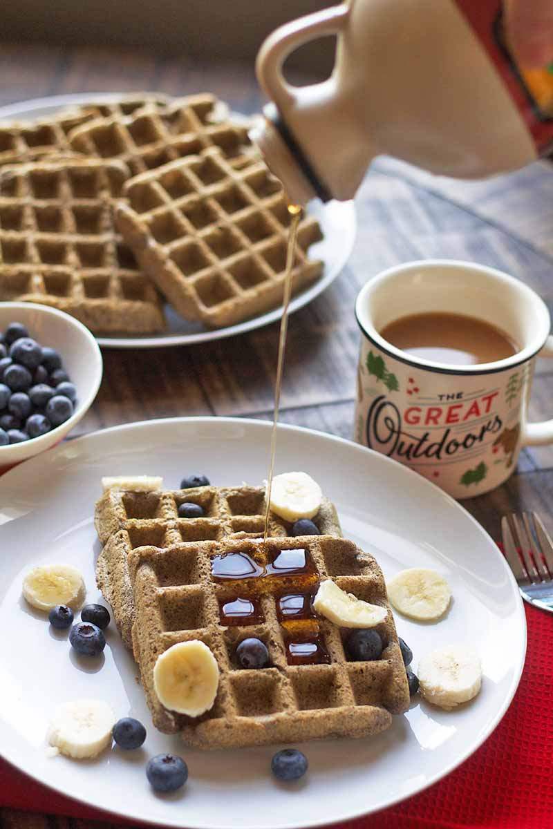 Vertical image of maple syrup being poured from a plastic pitcher-style bottle onto a plate of buttermilk buckwheat waffles with slices of banana and berries on top, with a mug of coffee, a small white bowl of blueberries, and a plate of more of the freshly made gluten-free breakfast items in the background, on a brown wood surface topped with a red cloth placemat.