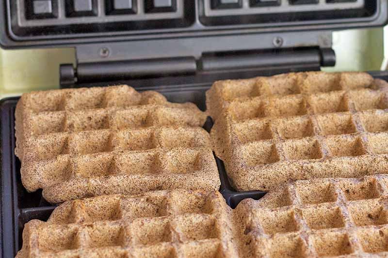 Closely cropped closeup horizontal image of freshly made waffles in an electric nonstick appliance.