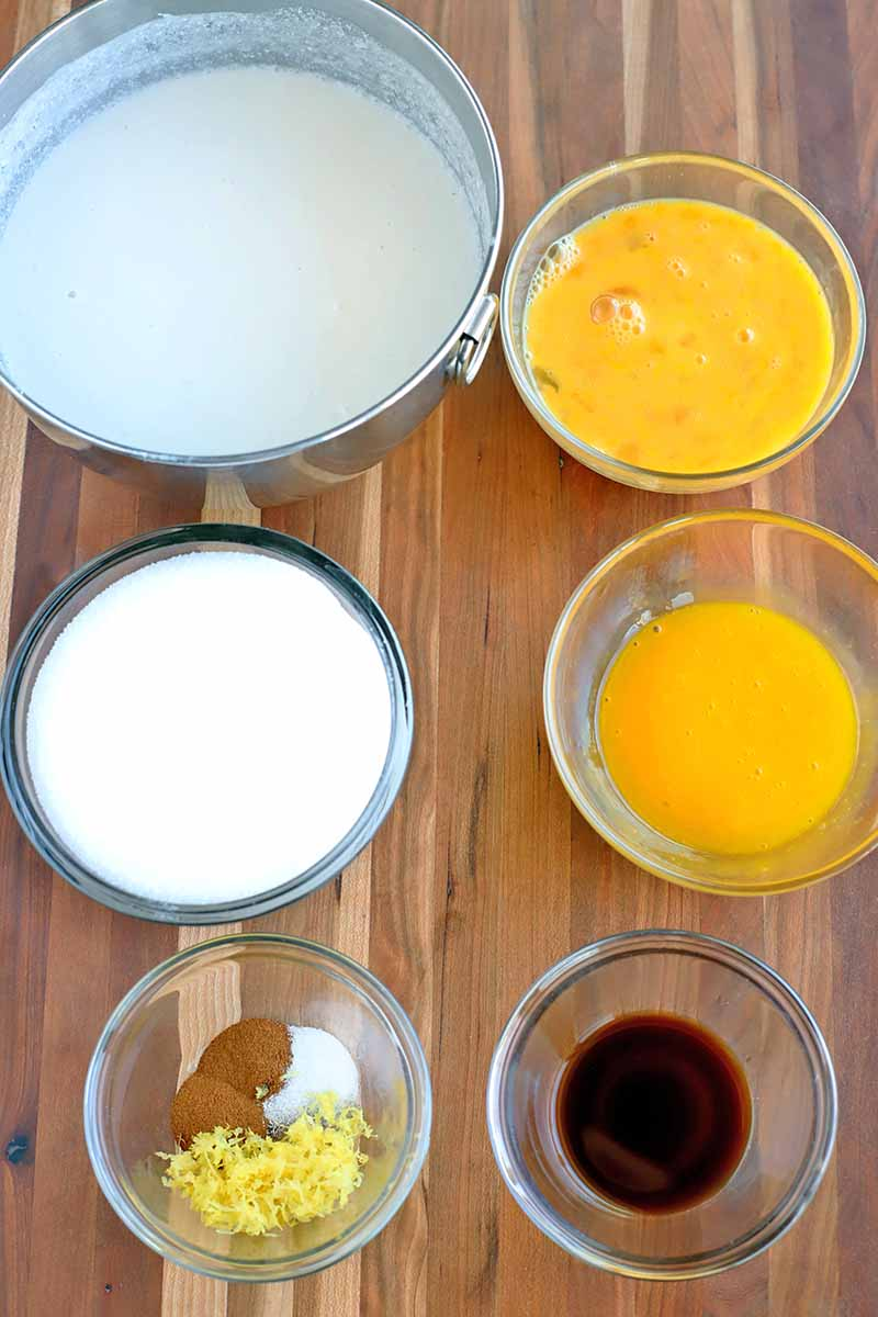 Overhead vertical shot of six glass and metal bowls of various sizes, containing coconut milk, beaten egg, sugar, spices, and vanilla extract, on a striped light brown wood surface.