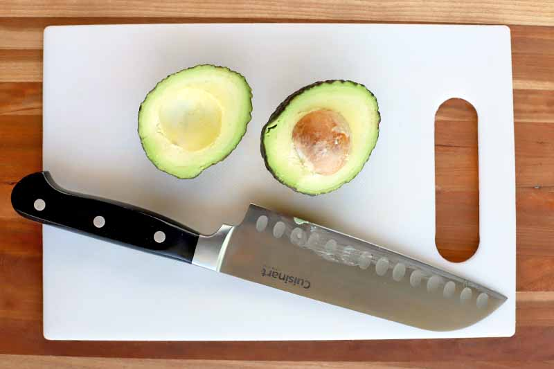 Horizontal overhead shot of a white plastic cutting board with a halved avocado and a knife with a black handle on top, on a wood surface.