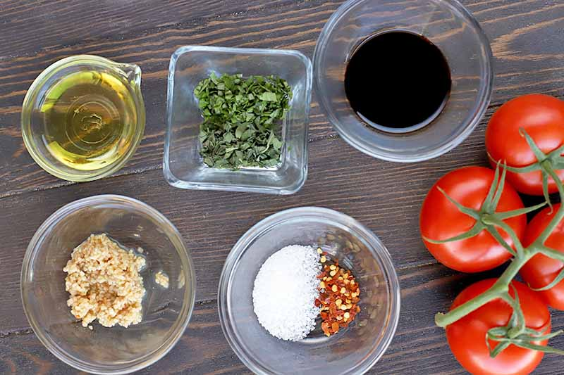 Overhead horizontal image of one small square and four small round glass bowls of olive oil, minced garlic, chopped herbs, balsamic vinegar, salt, and chili flakes, and four round red tomatoes on the vine, on a dark brown wood background.