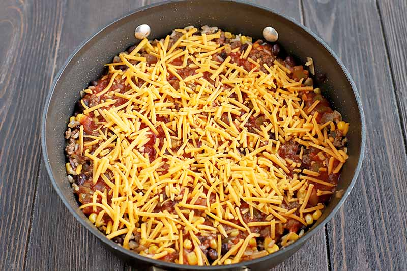 Overhead horizontal shot of a Tex-Mex skillet dish in a large frying pan with shredded yellow cheese on top, on a dark brown wood table.