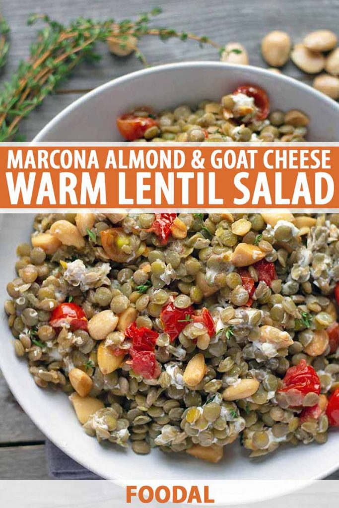 Vertical overhead image of a round white ceramic bowl of green lentil salad with goat cheese, almonds, thyme, and tomatoes, on an unfinished aged wood surface with scattered nuts and herb sprigs, printed with orange and white text in the middle and at the bottom of the frame.