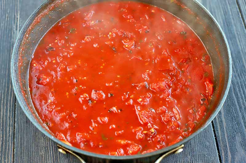 A large frying pan of red tomato sauce with steam rising from the surface, on a dark brown wood background.