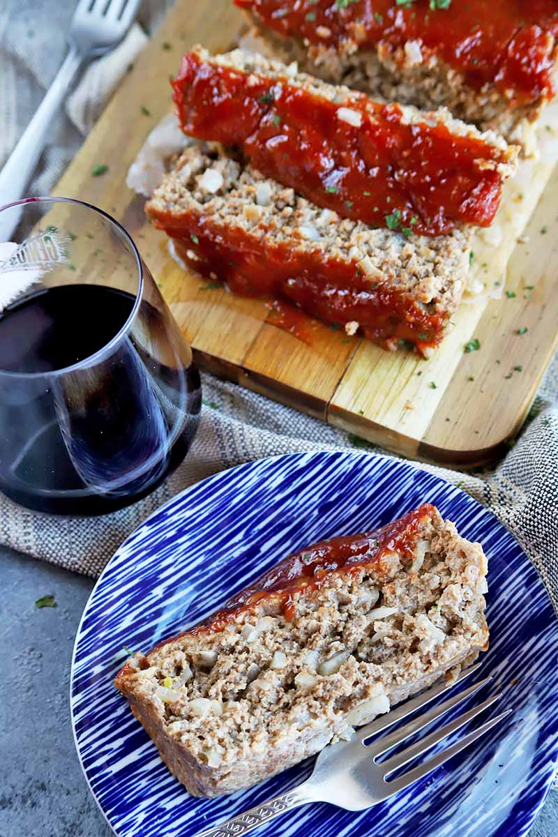Vertical image of a slice of meatloaf on a blue plate in front of a glaze of wine and the rest of the meal on a cutting board.