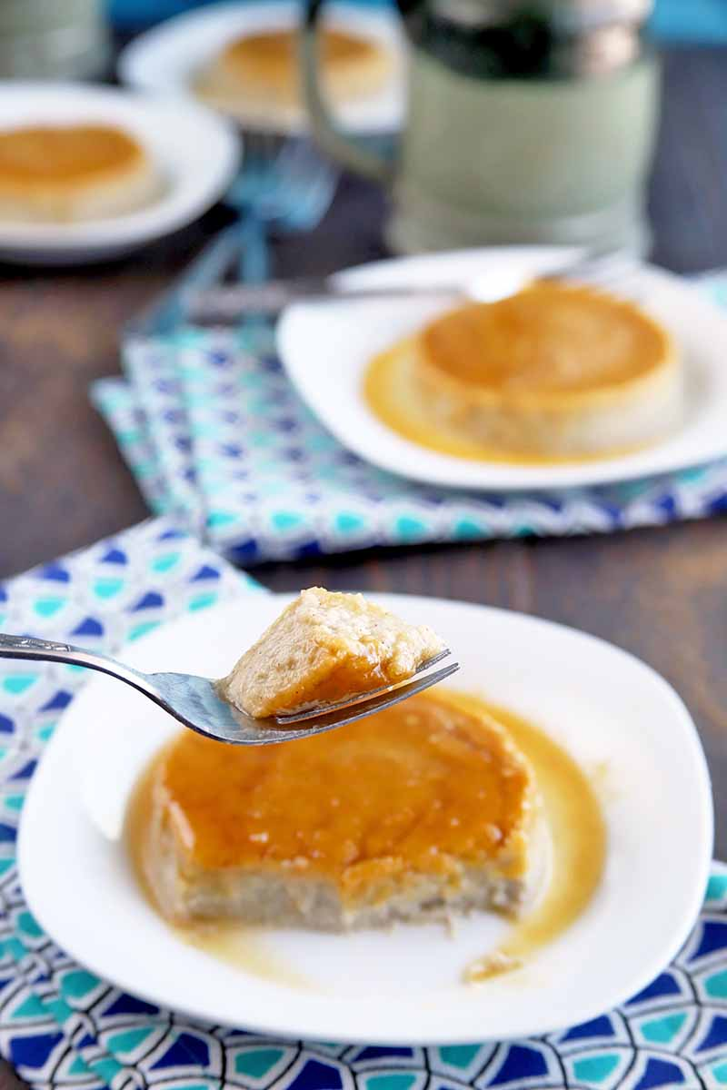 A forkful of homemade flan is held up to the camera, with plates of the dessert in teh background on a brown wood table with folded blue patterned cloth napkins and a gray ceramic mug.