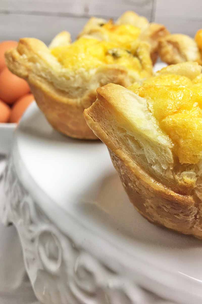 Vertical image of the buttery layers of puff pastry tarts on a white stand.