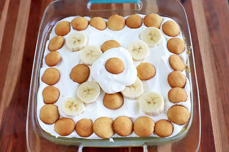 Oblique overhead horizontal shot of a square glass baking dish of banana cream pudding, with whipped cream, wafer cookies, and sliced fruit arranged to decorate the top, on a striped beige and brown wood surface with horizontal stripes.
