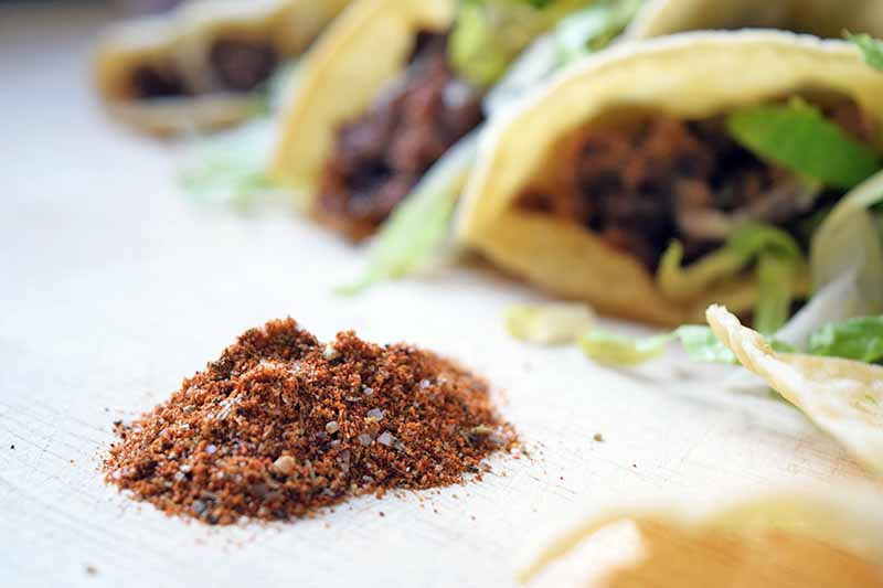 Horizontal image of a small pile of homemade taco spice mix in the foreground, with several beef tacos in hard corn tortilla shells in soft focus in the background, on a white surface.