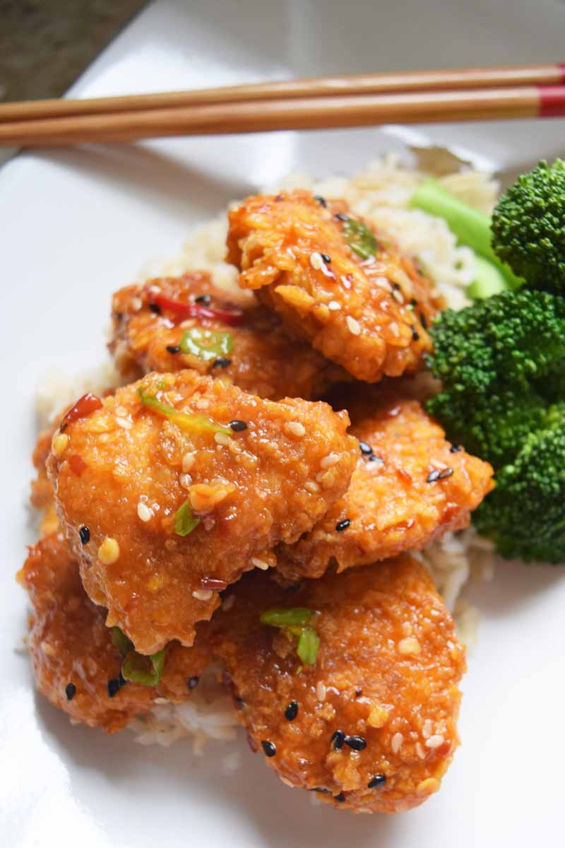 Oblique view of a light and baked General Tso's chicken dish on a white ceramic square dish.