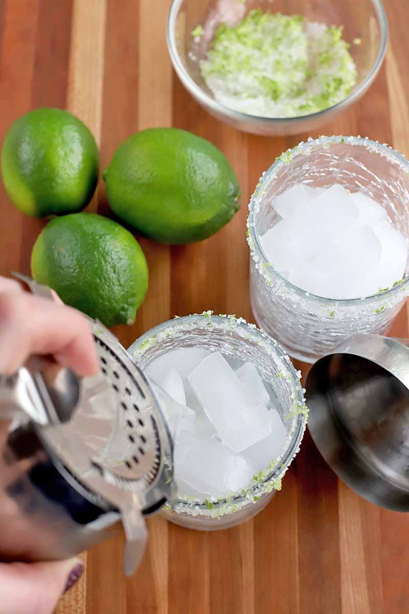 A hand with manicured and polished nails holds a strainer onto the top of a stainless steel cocktail shaker and pours a freshly made margarita into two lowball glasses filled with ice, with three limes, a citrus zest and coarse salt rimming mixture in a small glass bowl, and the top of the shaker, on a striped brown wood surface.