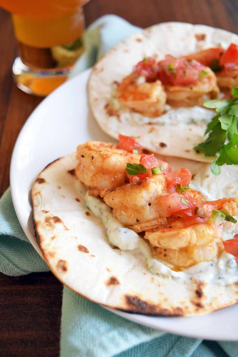 Horizontal slightly oblique head-on image of two shrimp tacos with cilantro and scallion crema, on a white plate with a sprig of fresh herbs, on a brown wood table with a folded pale blue cloth napkin and a beverage in a tall glass in the background.