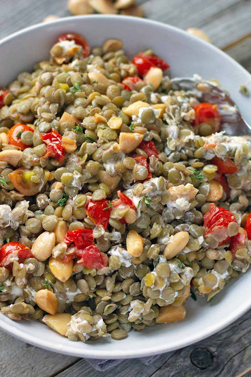 Closely cropped vertical overhead image of a white ceramic bowl of homemade lentil salad with crumbled goat cheese, chopped blanched Marcona almonds, chopped red cherry tomatoes, and fresh thyme, on a wood surface with scattered nuts and herbs in soft focus in the background.