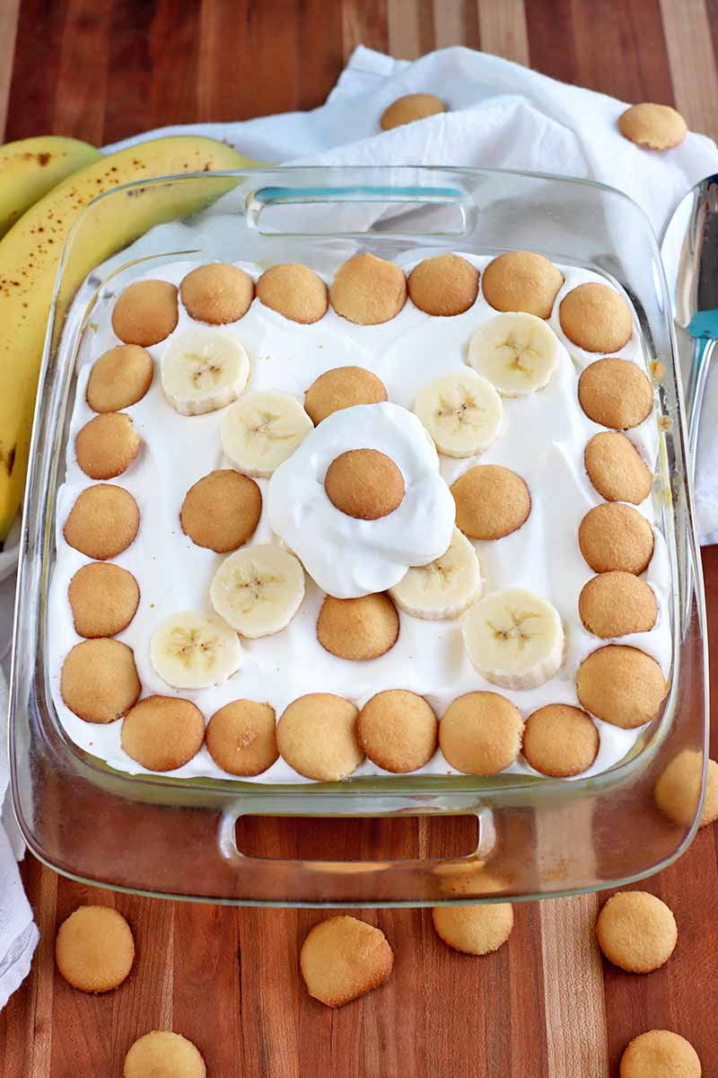 Vertical oblique overhead shot of a square glass baking dish with handles, filled with banana pudding with cookies and sliced fruit arranged on top for decoration, on a striped wood surface with a white folded cloth, two whole banana,s, and scattered vanilla wafers.