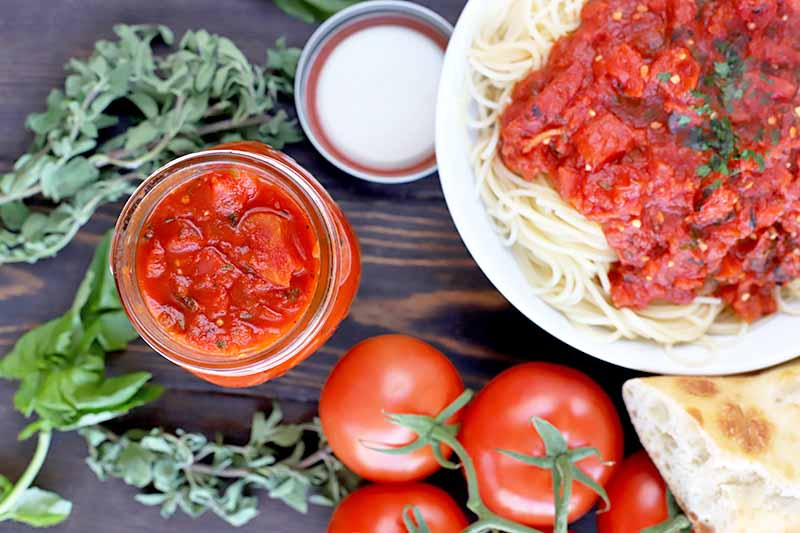 Overhead horizontal image of a mason jar of marinara with a metal lid, sprigs of basil and oregano, red tomatoes on the vine, a hunk of crusty bread, and a white plate of spaghetti topped with red sauce, on a dark brown wood surface.