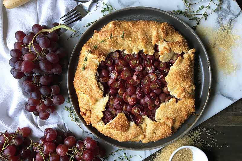 Horizontal image of a whole baked galette on a marble board next to whole grapes thyme leaves, sugar, and a metal fork.