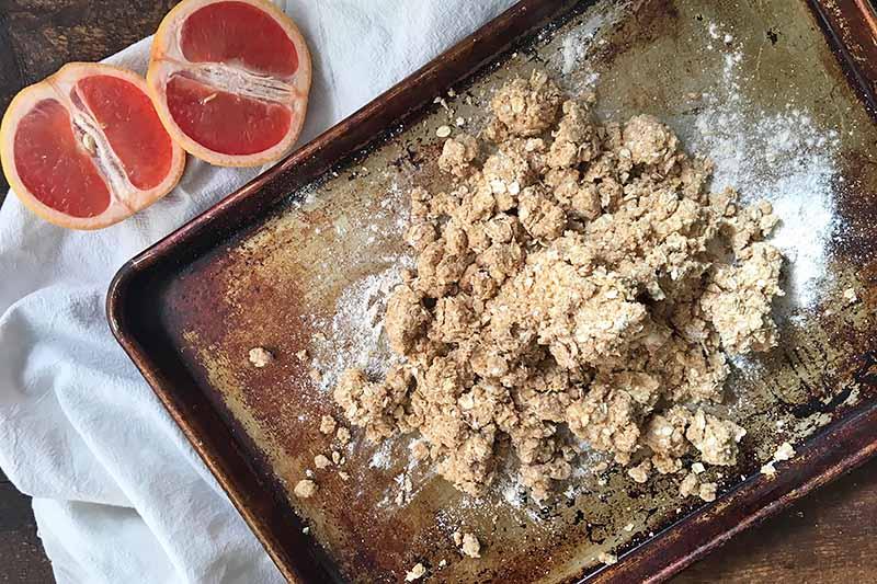 Horizontal image of a crumbly oat dough on a sheet pan next to grapefruit.