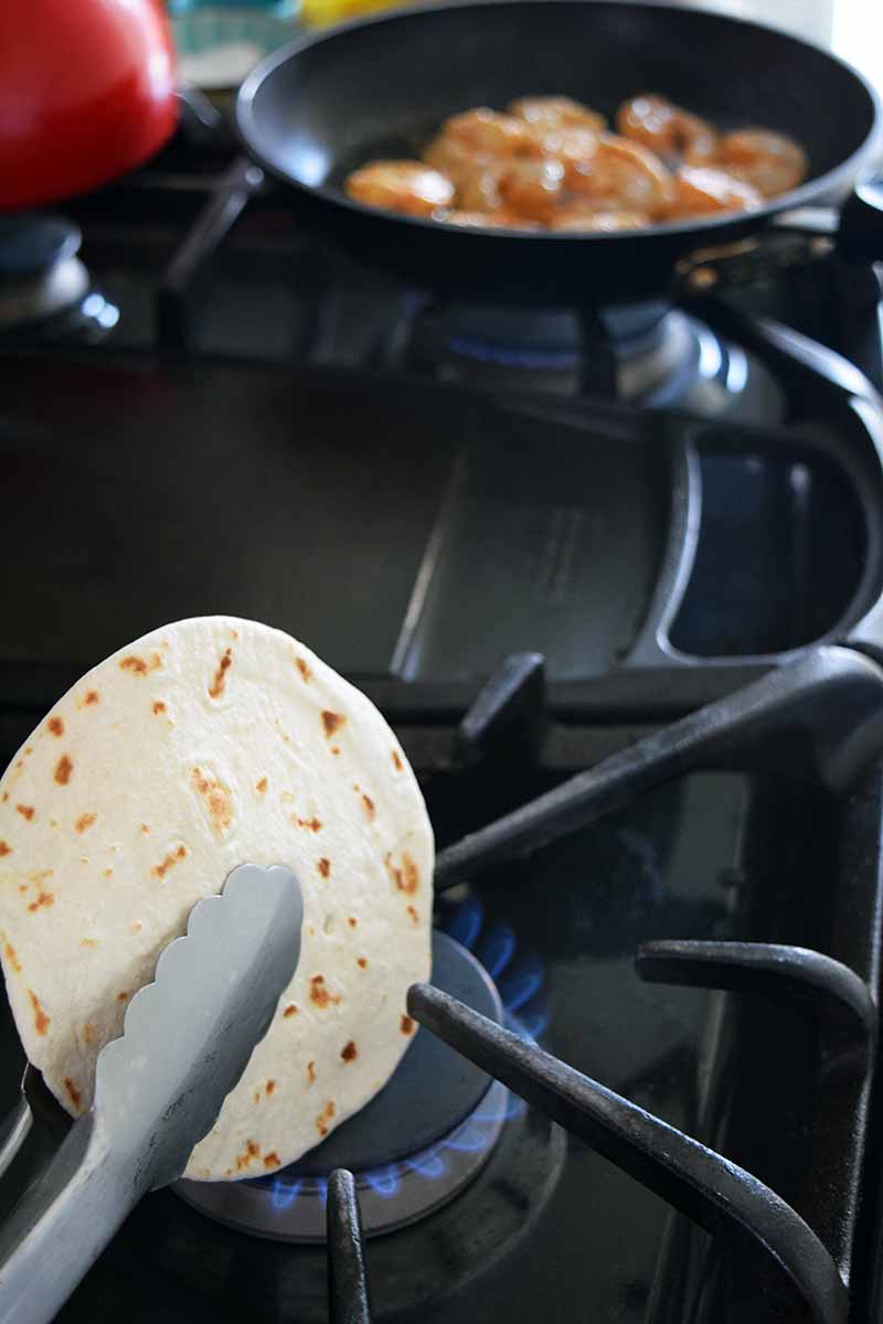 Vertical image of a set of metal tongs holding a flour tortilla over the blue flame of a gas stove, with shrimp cooking in a frying pan on the back burner beside a red tea kettle in soft focus.