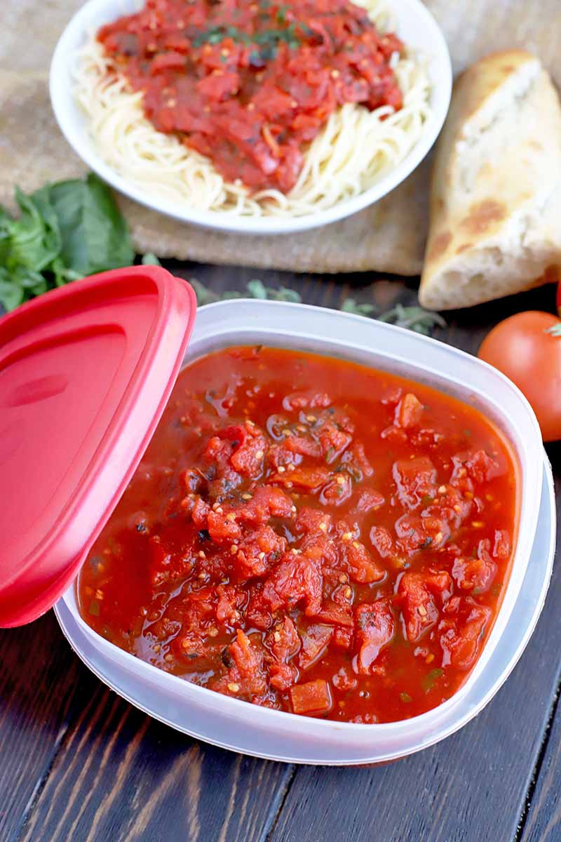 A square plastic container with a red lid filled with homemade tomato sauce, with a sprig of fresh basil and other fresh produce, a hunk of crusty bread, and a white plate of cooked pasta topped with marinara in the background on a piece of burlap, on a brown wood table.