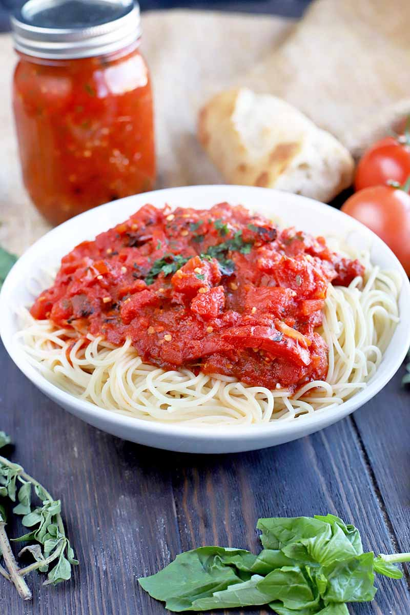 Vertical image of a white ceramic bowl of cooked spaghetti topped with chunky marinara, on a brown wood table with sprigs of fresh basil and oregano, and a piece of burlap in the background topped with a glass jar of red tomato sauce, a hunk of bread, and fresh produce.