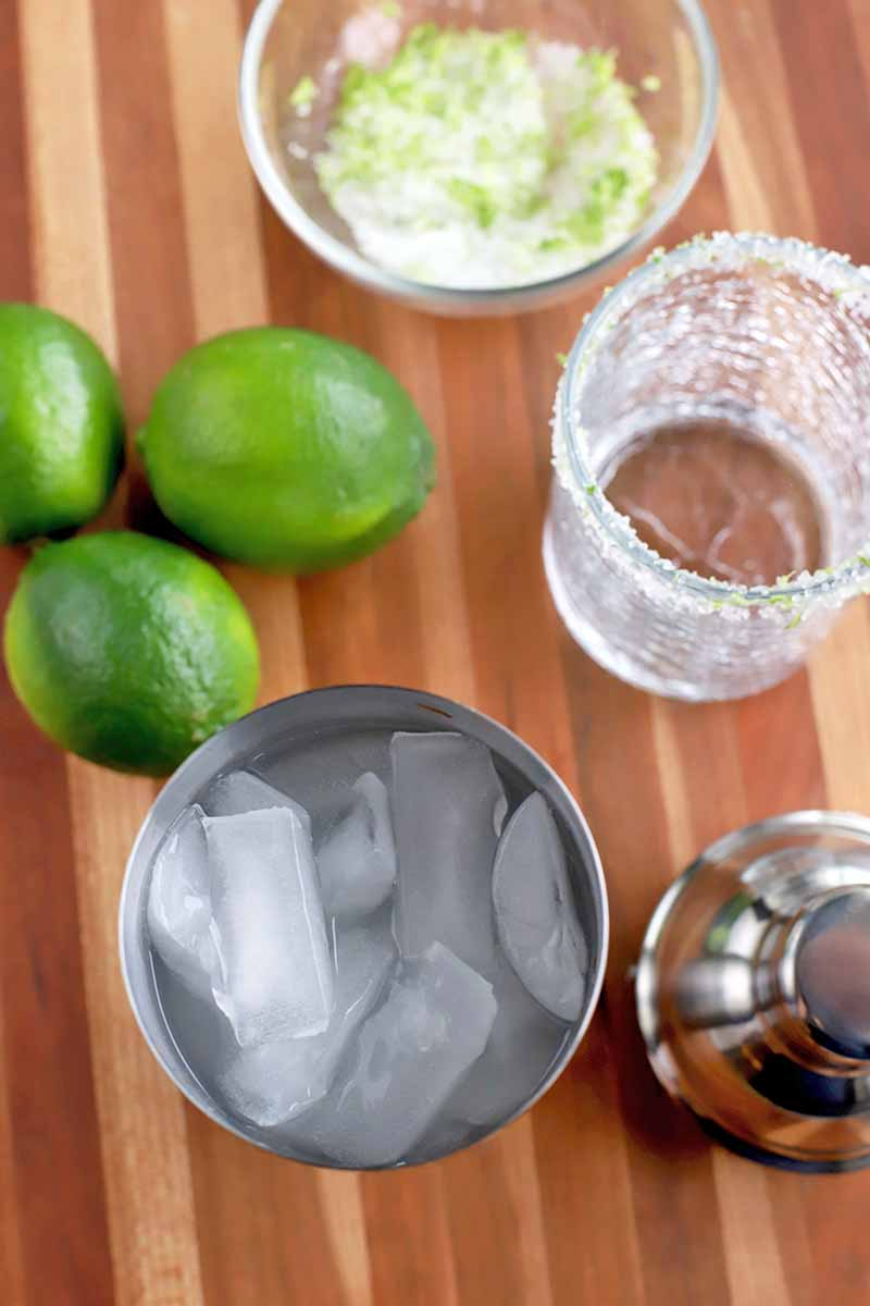 Overhead vertical image of a stainless steel cocktail shaker filled with ice, three limes, a small glass bowl of citrus zest and coarse salt, and a rocks glass, on a brown striped wood table.