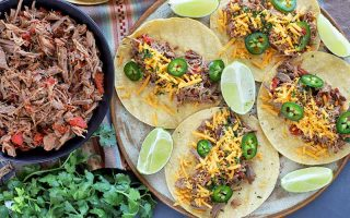 Overhead horizontal image of a black dish of shredded beef barbacoa with tomatoes to the left and a plate of tacos with the meat, shredded cheese, sliced jalapeno, and lime wedges to the right, with a bunch of fresh cilantro on a striped cloth, on top of a gray surface.