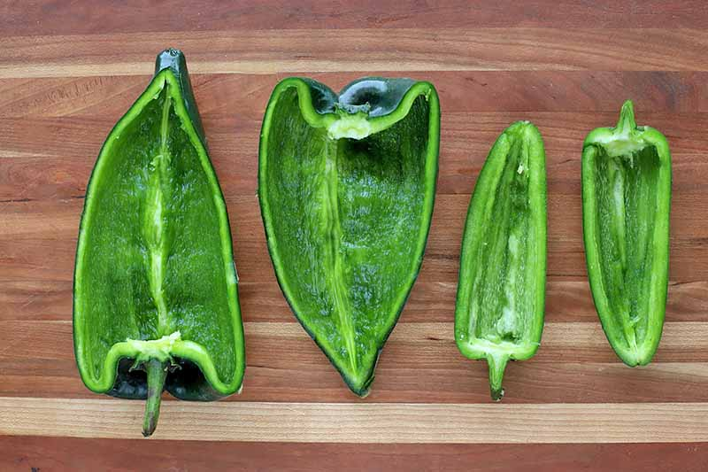 Horizontal image of cut and seeded green peppers on a wooden cutting board.