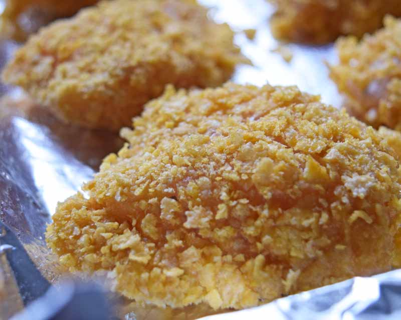 Close up of a piece of raw, breaded chicken on a baking tray. Oblique view.