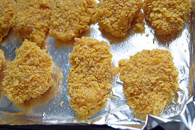Top down view of baked breaded chicken pieces on an aluminum foil lined baking tray.