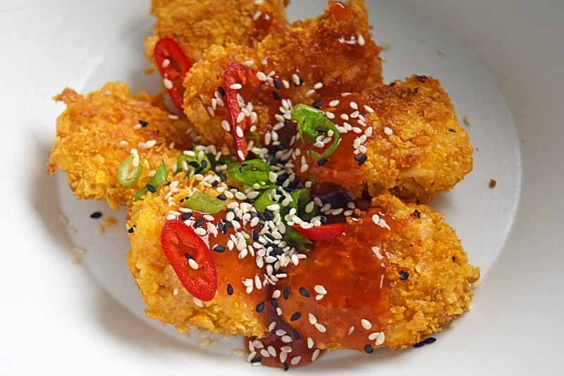Bake breaded chicken chunks with sauce, chilies, sesame seeds, and scallions applied on top.