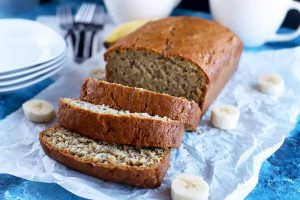 Horizontal head-on image of a loaf of banana bread with three cut slices arranged on a crumpled piece of white parchment paper with sliced fruit, to the right of a stack of white plates, with forks and white teacups in the background, on a blue surface.