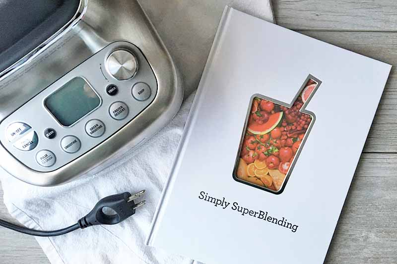 Horizontal image of a recipe book next to a blender on a white towel.