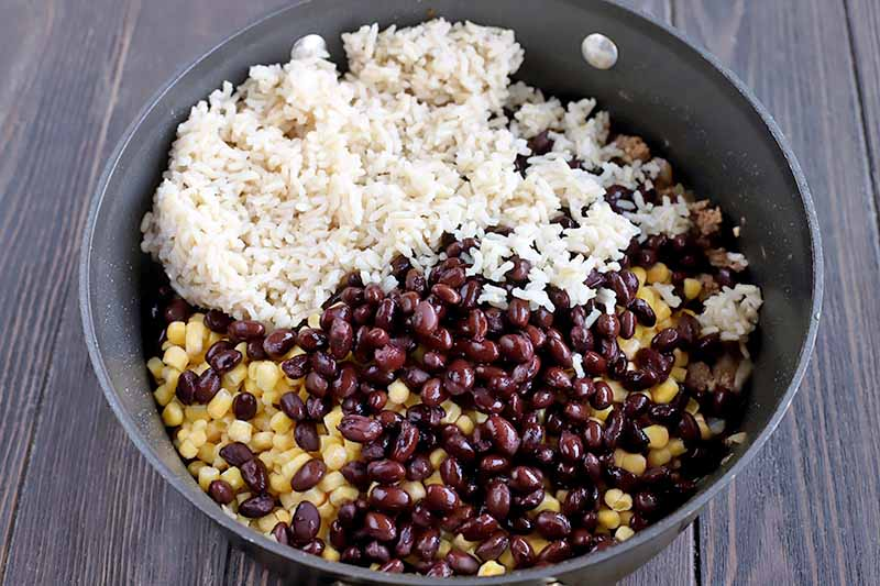 Overhead shot of a large frying pan with high walls, filled with black beans, corn, and rice, on a dark brown wooden table.
