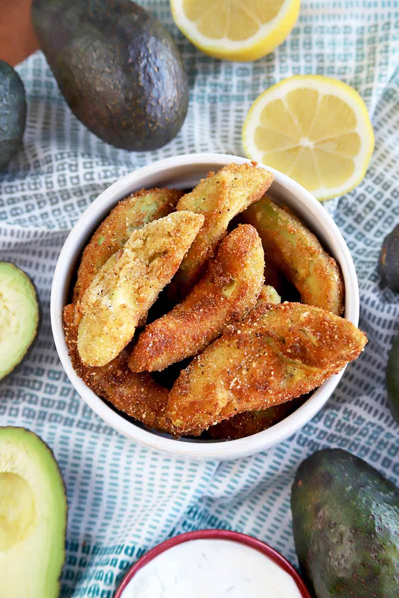 Vertical overhead shot of a small white bowl of avocado fries, with whole and sliced pieces of the raw fruit surrounding the dish, and two halves of lemon, with a small bowl of tzatziki dip at the bottom of the frame, on a light blue and white cloth, on top of a brown wood table.