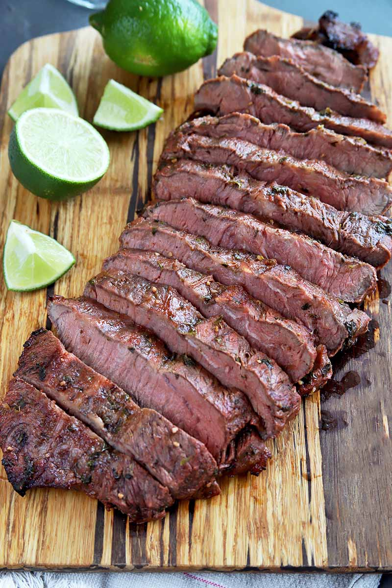 Vertical image of sliced steak on a wooden cutting board by limes.