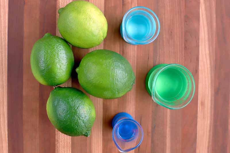 Overhead horizontal shot of four green limes and three glass measuring beakers in shades of blue and green, on a wood surface with vertical stripes.