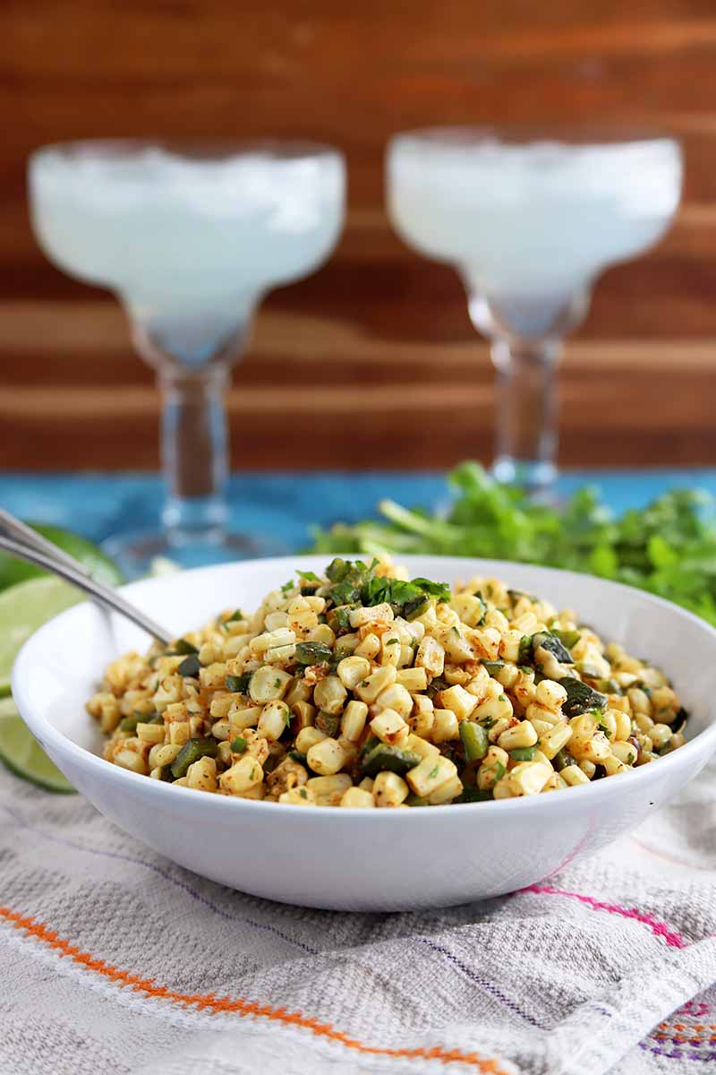 Vertical image of a bowl of corn salad, with margarita glasses behind it.