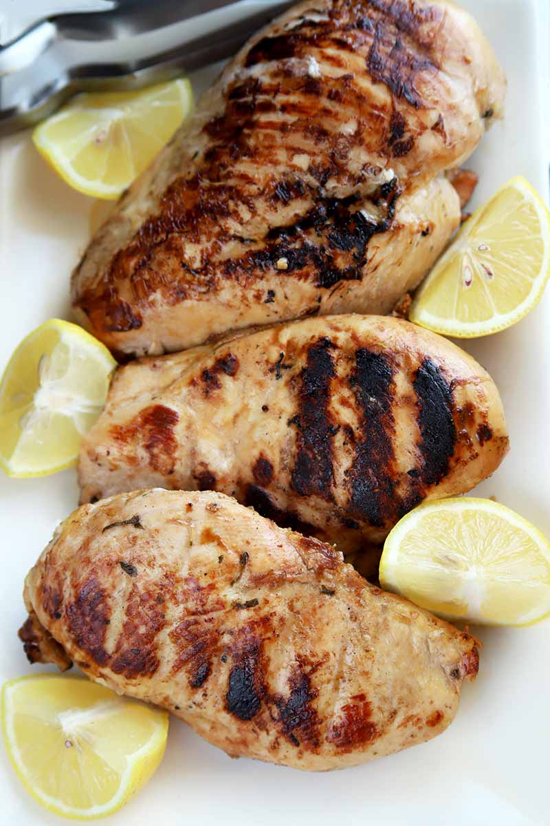 Vertical overhead shot of four grilled, boneless, skinless chicken breasts with five wedges of lemon on a white ceramic serving platter, with metal tongs.