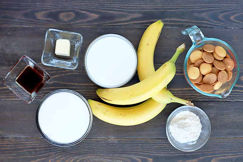 Overhead horizontal image of two square glass bowls of butter and vanilla extract, three round glass bowls of sugar, cream, and milk, and a glass measuring pitcher of wafer cookies, with three whole yellow bananas, on a dark brown wood surface.