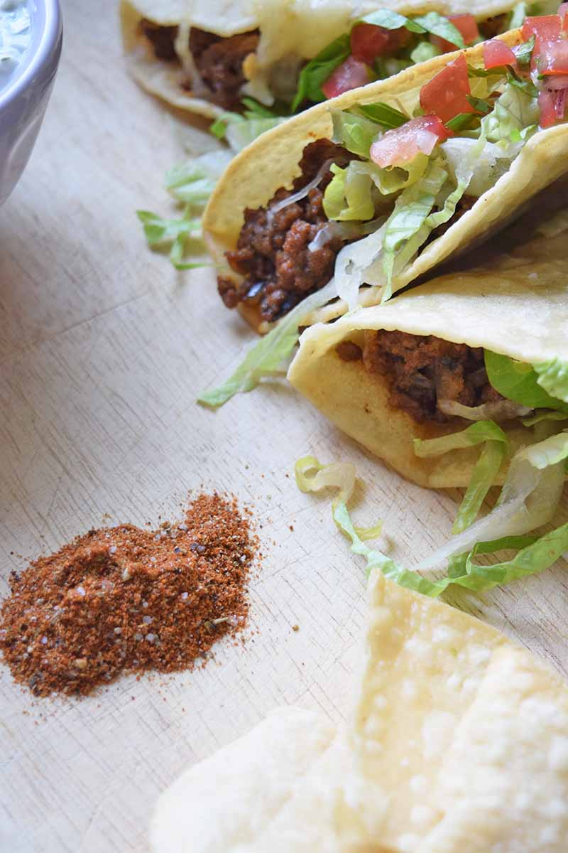 Overhead closely cropped vertical overhead oblique image of several beef tacos to the right, a few fried corn tortilla shells at the bottom right, and a small pile of an orange-colored spice mixture to the bottom left, on a beige wood surface.