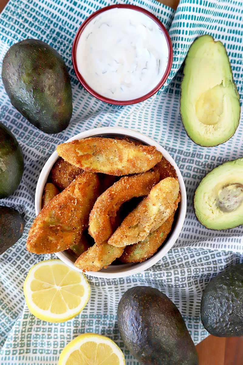 Overhead shot of whole, halved, and batter-dipped and fried avocado, on a light blue and white cloth-covered surface with a lemon that has been cut in half, and a small dish of tzatziki.