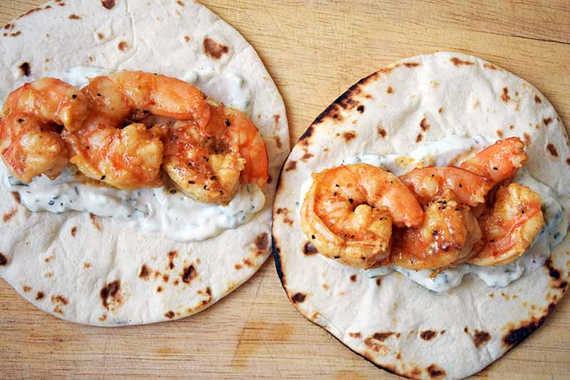 Overhead horizontal image of two flour tortillas topped with three marinated and pan-fried shrimp each, arranged on top of a smear of cilantro and green onion crema, on an unfinished wood cutting board.