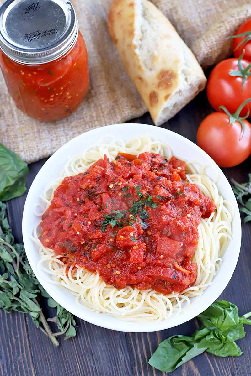 Vertical image of a white plate of spaghetti marinara, on a brown wood table partially covered with a piece of tan-colored burlap, with a glass jar of red sauce, a hunk of bread, several fresh tomatoes on the vine, and sprigs of basil and oregano.