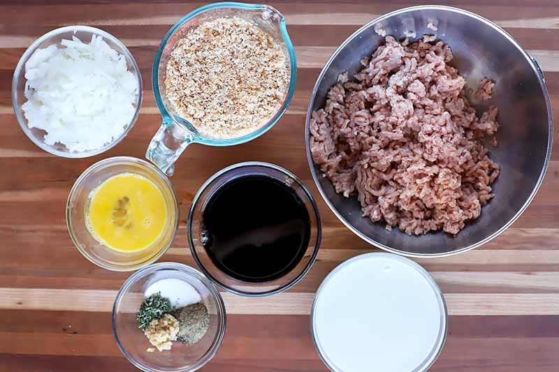 Horizontal image of ground turkey, breadcrumbs, vinegar, and other ingredients in various bowls on a wooden surface.