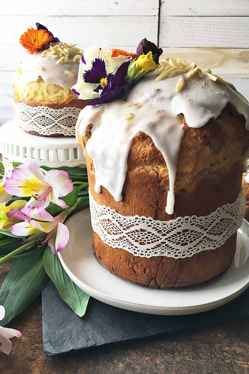 Vertical image of two kulich loaves with white icing, ribbons wrapped around it, and floral decor.