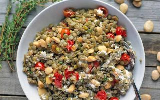 Overhead closely cropped horizontal image of a white bowl of homemade lentil salad with nuts, cheese, and tomatoes, with a serving spoon, on a wood surface with fresh thyme and Marcona almonds.