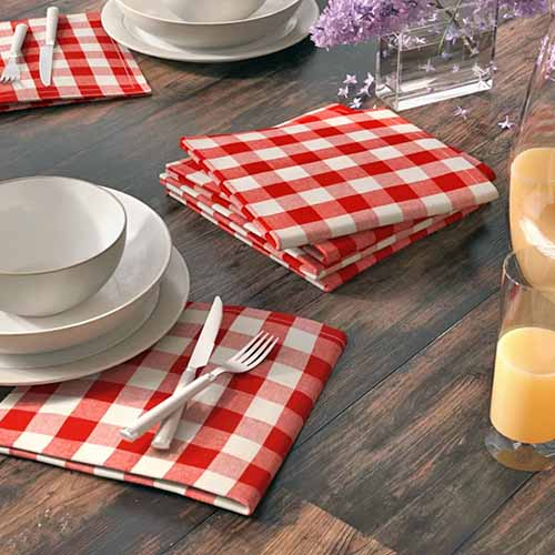 Arlington checkered napkins sit on a table with cutlery and bowls.